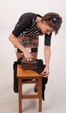 Sparato di una giovane donna divertente che prova a rivestire di ferro i suoi vestiti fotografia stock