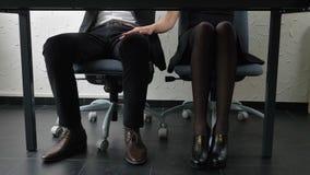 Sparato sotto la tavola, una giovane ragazza del capo tocca il suo piede del ` s degli impiegati, i flirt, fps di concetto 50 di  archivi video