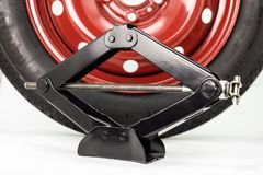 Spare car tire on steel, red rim and manual scissor car jack, isolated on a white background with a clipping path. stock image