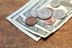 Spare change. Dollars and cents over wood background Stock Photography