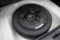 Spare tire. In the trunk of a modern car Stock Photos