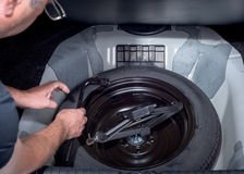 Spare tire with jack in trunk of a car Stock Photography