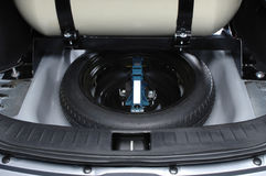 Spare wheel in car trunk. Gas tank and spare wheel inside car trunk, showing enough space royalty free stock photography