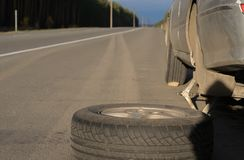 Spare wheel lying near the car. The car is mounted on the Jack. View asphalt road at sunset stock photography