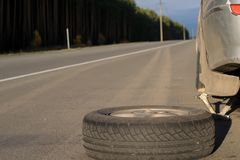 Spare wheel lying near the car. The car is mounted on the Jack. View asphalt road at sunset stock image