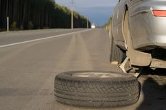 Spare wheel lying near the car royalty free stock images