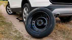 Spare wheel next to the broken car on countryside dirt road stock footage