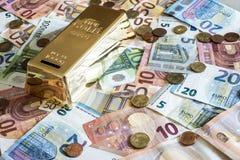 Spareinlagen-Bargeldkonzept-Eurobanknoten alle Größen- und Centmünzen auf Schreibtischsparschweingoldbarren-Formabwehr Stockbilder