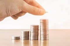 Sparen geld met het muntstuk van het stapelgeld voor het kweken van uw zaken stock foto