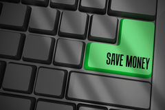 Sparen geld op zwart toetsenbord met groene sleutel Stock Foto's