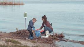Sparen planeet, meldt de jonge moeder zich met zoon schoon verontreinigd strand van plastic afval dichtbij water op rivierdijk aa stock footage