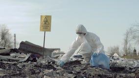 Sparen planeet sparen planeet van afval, Hazmat-verzamelt de onderzoeker in beschermende eenvormig afval in vuilniszak voor het t stock video