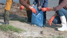 Sparen planeet van plastiek, verzamelt de jonge familievrijwilligers met jong geitje in rubberhandschoenen afval in vuilniszak te stock videobeelden