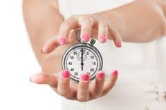 Sparen tijdconcept Twee Vrouwenhanden die Chronometer beschermen Stock Afbeeldingen
