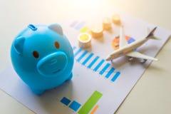 Sparen uw geld voor reis Spaarvarken met muntstukken, vliegtuig en financiële documenten stock afbeeldingen