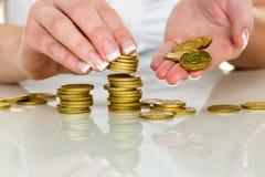 Sparen vrouw met stapel muntstukken op geld Royalty-vrije Stock Foto