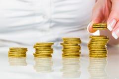 Sparen vrouw met stapel muntstukken op geld Stock Foto's