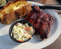 Sparerib Dinner. Barbequed spareribs served with a baked potato and coleslaw, on a picnic table out on the patio royalty free stock images