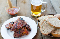 Spareribs on grill with hot marinade, czech beer Royalty Free Stock Photos
