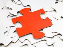 Séparez le morceau rouge sur la pile des puzzles denteux blancs Images libres de droits