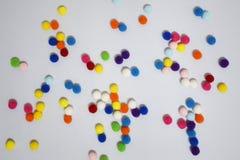 Sparga i poms dolci del pom di colore di pendenza su fondo bianco fotografia stock libera da diritti