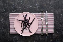 Spargel-Bohnenhülsen des diätetischen Lebensmittels purpurrote auf rosa Platte Stockfoto