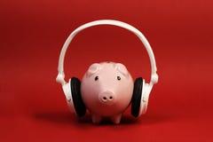 Spargris med det vita hörlurar med mikrofonanseendet på röd bakgrund royaltyfri fotografi