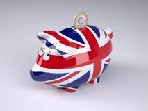 Spargris med engelskaflaggan och det fullödiga myntet Arkivbilder