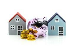 Spargris med huset och bunten av mynt som sparar för att köpa ett hus, arkivfoto