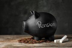 Spargris med ordet PENSION, krita och mynt på tabellen arkivfoton