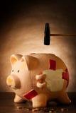 Spargris med pengar och hammaren Royaltyfri Foto
