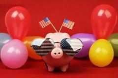 Spargris med retro solglasögon med USA flaggan och två lilla USA flaggor och ballonger många färger på röd bakgrund Arkivfoto