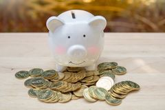 Spargris och hög många pengarmynt på en trätabell - Spara pengar med buntpengarmyntet för att växa, spara pengarbegrepp arkivbilder