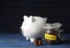 Spargris och krus av mynt med ordet PENSION royaltyfria bilder
