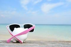 Spargris och sunglass på tabell- och havsbakgrund Fotografering för Bildbyråer