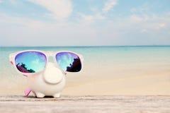 Spargris och sunglass på tabellen och havet Royaltyfri Bild