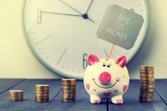 Spargris- och tornmynt på bakgrund av klockan Inskriften Tid är pengar kopiera avstånd Royaltyfri Fotografi