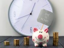 Spargris- och tornmynt på bakgrund av klockan Inskriften Tid är pengar kopiera avstånd Arkivfoton