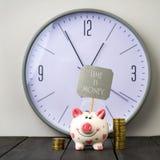 Spargris- och tornmynt på bakgrund av klockan Inskriften Tid är pengar kopiera avstånd Royaltyfri Foto