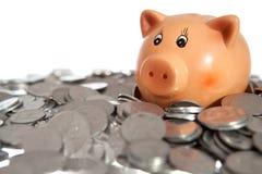 Spargris på en hög av mynt royaltyfri foto