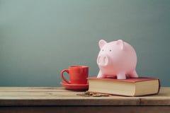 Spargris på trätabellen med den kaffekoppen och boken piggy sättande sparande för grupppengar royaltyfri foto