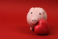 Spargris som är förälskad med röd hjärta på röd bakgrund Arkivbilder