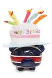 Spargris som bär en hatt för lycklig födelsedag Arkivfoton