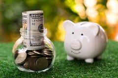Spargris som ser på exponeringsglas av kruset som fulled av pengar besparingar för pengar för flaskbegreppsdollar royaltyfria foton