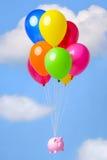 Spargris som svävar till och med himlen på ballonger arkivfoto