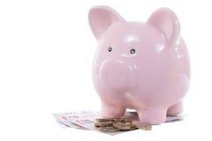 Spargrisanseende på en hög av UK-pengar royaltyfri foto