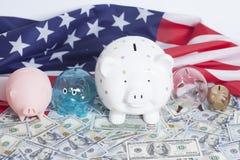 Spargrisar på dollar med amerikanska flaggan Arkivfoto