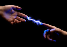 Spark between hands Stock Photo