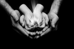 Spark of hope in a child hands wh holding by parents handson dark background. The light of faith Royalty Free Stock Photos