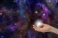 The Spark of Life. Gyan Mudra Hand Position creating the Spark of Life on a deep space background with planets, stars, suns, clouds and plenty of copy space